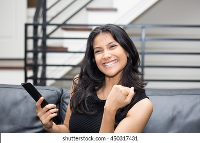 Closeup portrait, young woman in black shirt, sitting on leather couch fists pumped, watching TV, holding remote, thrilled at what she sees, isolated indoors flat background