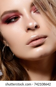 Close-up portrait of young woman with dark red smokey eyes. Modern fashion make-up. Studio shot