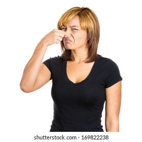 Closeup portrait of young woman with disgust on her face who covers pinches her nose looks at you, something stinks, very bad smell, situation, isolated on white background. Human emotion, expression.