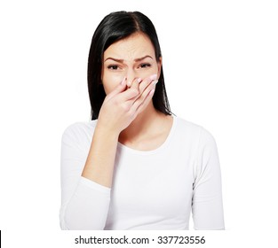 Closeup portrait young woman, disgust on face, pinches nose looks funny, something stinks, very bad smell, situation, isolated white background. Negative emotion, facial expression, feeling reaction