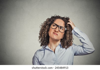 Closeup portrait young woman with glasses scratching head, thinking daydreaming something looking up isolated grey wall background. Human facial expression emotion feeling body language perception