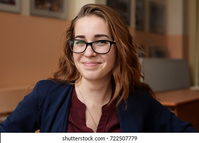 Close-up portrait of a young woman in glasses. A girl with red hair in the classroom. Business woman in training class