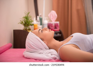 Close-up portrait of a young woman with a healthy and clean skin, with a towel on her head lying on a table in healthy beauty spa salon looking up