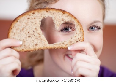 Closeup portrait of young woman looking through heart shaped hole in bread