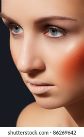 Closeup portrait of young woman model with bright glamour make-up, orange blusher, rouge, shiny skin. Clean female look