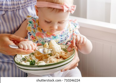 Closeup portrait of young woman mother feeding her girl daughter with vegetables broccoli cauliflower. Healthy organic food for children. Candid lifestyle family life. Baby trying finger food
