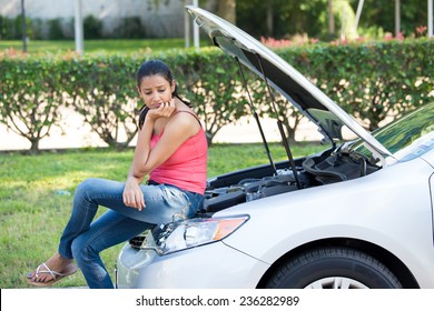 Closeup portrait, young woman in pink tanktop having trouble with her broken car, sitting on open hood engine worried, isolated green trees and shrubs outside background