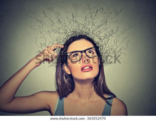 グレイの背景に見上げた疑問符に、頭をかきむしる若い女性の接写、頭をかきむしる考え。人間の表情、感情の表情