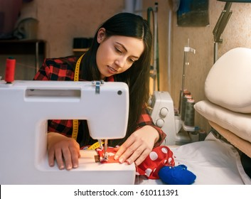 closeup portrait of young woman seamstress sitting and sews on sewing machine. Tailor making a garment in her workplace. Hobby as a small business concept