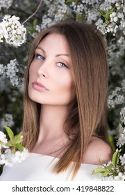 Closeup portrait of young woman in spring blossoming garden. Nude makeup, blue eyes. The flowers in the background