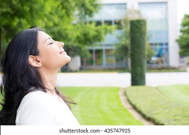 Closeup portrait, young woman in white shirt breathing in fresh crisp air after long day of work, isolated outdoors outside background. Stop and smell the roses, connect with nature