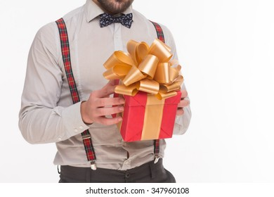 Close-up portrsit of New Year of Christmas present or gift. Man in white shirt and bow tie holding present or girt in front of him.