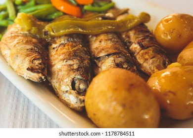 Close-up of portugese traditional grilled sardines sardinas on a plate with potatoes and vegetables, in Lisbon, Potrugal