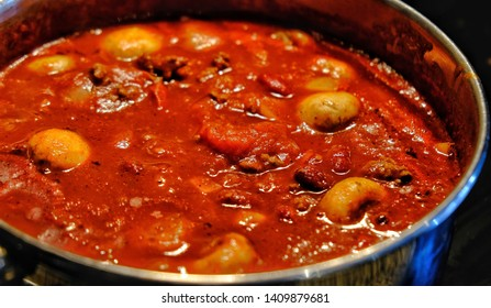 Closeup of a pot of Chile con carne simmering on stove.