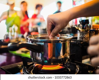 closeup of a pot on gas stove during a thai cooking class with hands