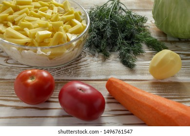 The closeup potatoes cut into long slices are placed in a glass transparent baking dish. The process of cooking the Orlov-style meat. Lying next to the whole clean vegetables. Vintage wooden backgroun