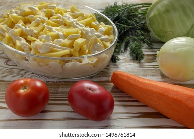 The closeup potatoes cut into long slices are placed in a glass transparent baking dish with drops of mayonnaise. The process of cooking the Orlov-style meat. Lying next to the whole clean vegetables.