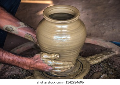 Closeup of potter's hands making clay water pot on pottery wheel. Clay pots are used since ancient times and can be found in Indian subcontinent.