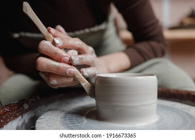 Closeup of potter's hands molds clay pot spinning on pottery wheel with special wooden tool. Woman works with tools in pottery workshopCloseup of potter hands molds clay pot spinning on pottery whee