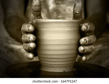 Close-up of potter's hands with the product on a potter's wheel