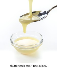 closeup pouring condensed milk with teaspoon