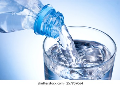 Close-up Pouring glass of water from a plastic bottle on blue background