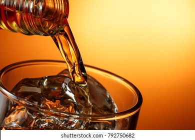 closeup of pouring whiskey against orange gradient