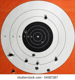 A Closeup of a practice target used for shooting with bullet holes in it.