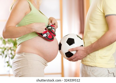 Close-up of a pregnant woman with childen boots and her husband holding a soccer ball