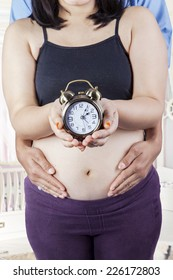 Closeup of pregnant woman and her husband showing a clock in the bedroom