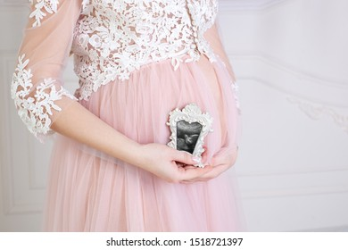 Closeup of pregnant woman holding an ultrasound scan on her tummy. pregnant woman enjoys the first photo of her unborn baby in frame, anticipating her future life copy space. Healthy pregnancy concept
