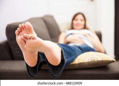 Closeup of a pregnant woman lying on a couch with swollen feet. Focus on feet