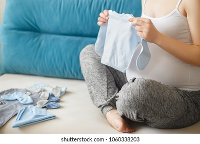 closeup of pregnant woman preparing clothes for newborn. Expectant mother holding baby's loose jacket