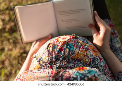 Closeup of pregnant woman reading book in nature
