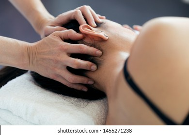 Close-up of pregnant woman receiving osteopathic or chiropractic treatment in neck in a clinic.