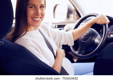 Closeup of pregnant woman turning to camera while sitting at wheel