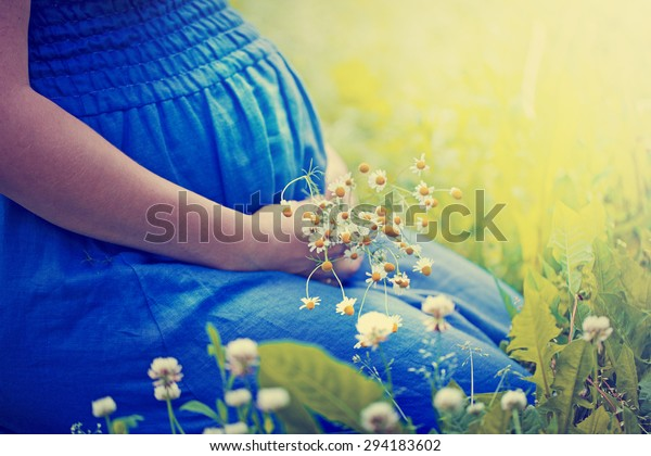 Closeup of pregnant woman, wearing blue dress, holding in hands bouquet of daisy flowers outdoors, new life concept