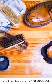 Close-up of Premium Tan Brogue Leather Boot with Set of Cleaning Accessories,Wax  and Cloth. Vertical Image Orientation