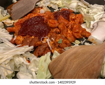 Closeup to prepare chicken Galbi Korean stir fried with tokpokki, mushrooms, chopped chicken and vegetables with Korean red sauce (gochujang) in pan with pare of  wooden cooking paddle