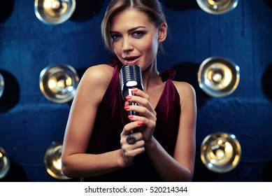 Close-up of pretty appealing woman who is singing with a microphone in a studio lighting. Using the classical vintage standing microphone