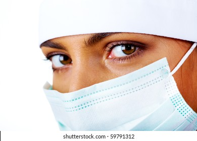 Close-up of pretty assistant in mask looking at camera
