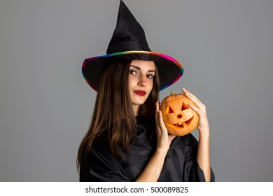 closeup of pretty brunette woman in halloween style clothes with pumpkin in hands looking at the camera in studio on grey background