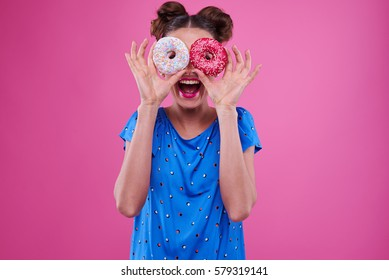 Close-up of pretty girl with double buns looking through the two sprinkled donuts isolated over pink background