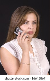 closeup of pretty hispanic model on cell phone isolated on black