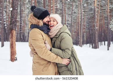 Close-up of pretty married couple. Man and woman wrapped in a warm winter clothes walking in the forest in a cold weather. Hugging each other and looking at the camera