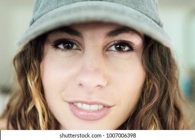 Close-up of pretty sexy woman wearing baseball cap with brunette wavy hair.