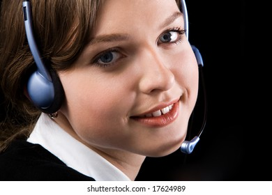 Close-up of pretty woman face with headset looking at camera and smiling