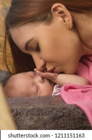 Close-up pretty woman kisses a newborn baby in her arms