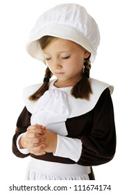 "Closeup of a pretty young elementary ""pilgrim"" girl in prayer.  On a white background."