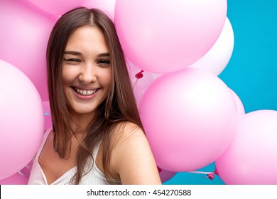Close-up of pretty young girl winking at camera while taking self-portrait in pink balloons